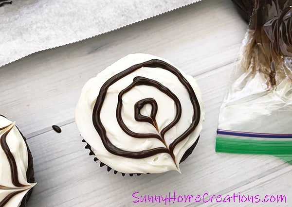 Spider web cupcakes with spider web rings piped on