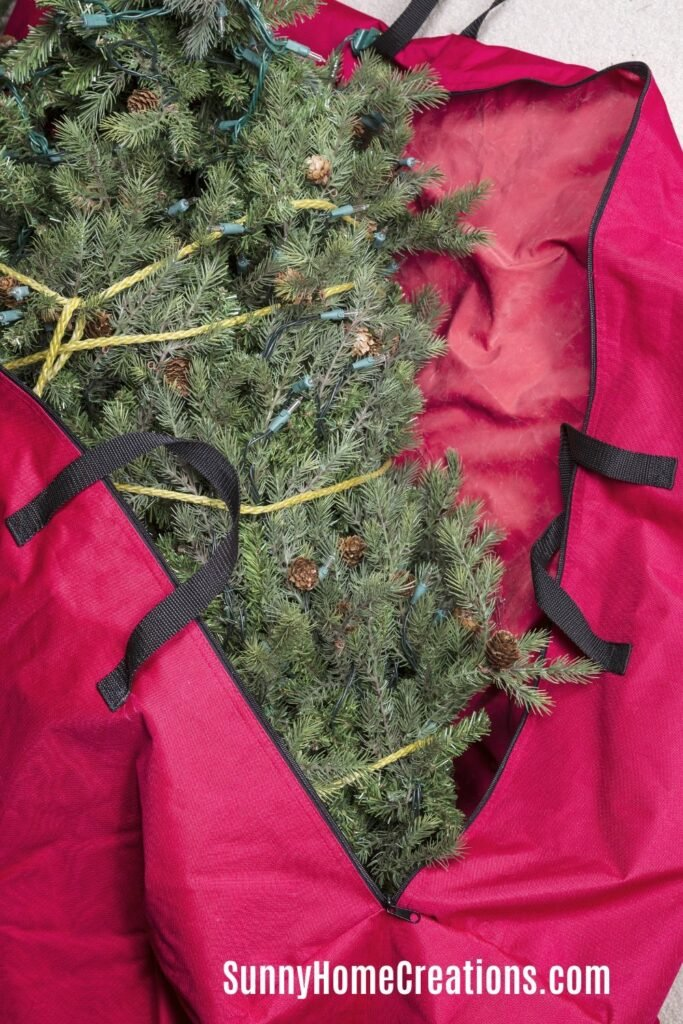 artificial Christmas tree being put into storage bag