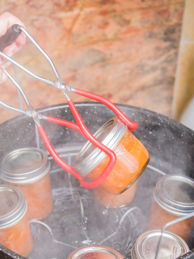 a jar lifter being used to remove a mason jar from a water bath canner.