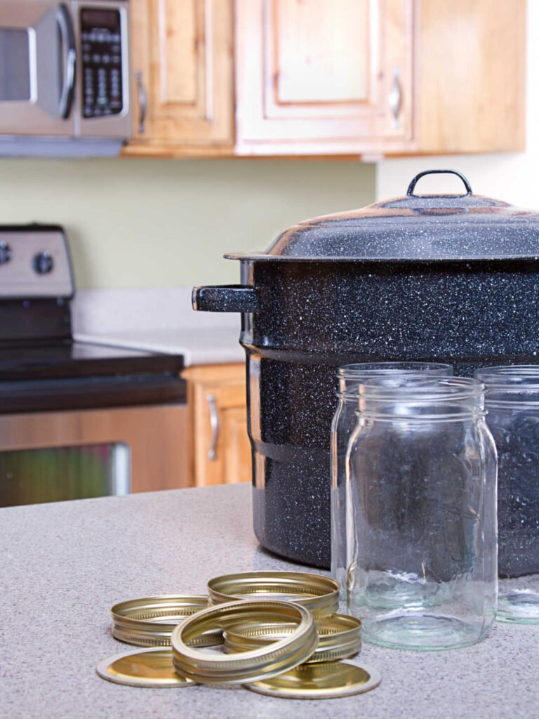 water bath canner, a couple mason jars in front of it with a pile of lids and bands next to them.