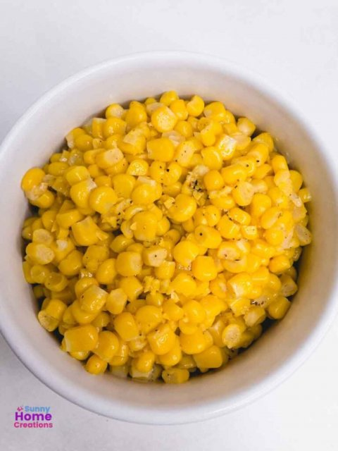 top down view of cooked canned corn in a bowl.