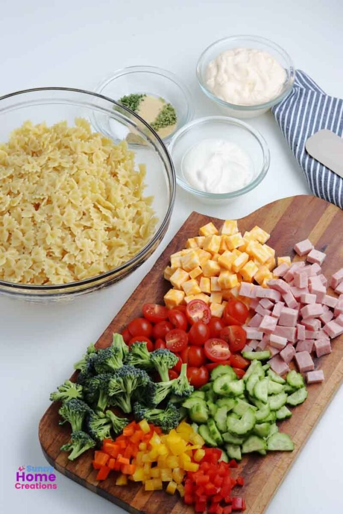 bowl of bowtie pasta noodles, small bowl of seasoning, small bowl of sour cream, small bowl of mayonnaise, cutting board with cut up cheese, ham, cherry tomatoes, cucumbers, bell peppers, and broccoli on it.