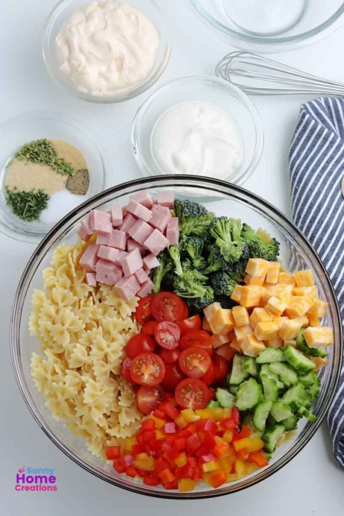 small bowl of mayonnaise, small bowl of sour cream, small bowl of spices, and bowl with diced ham, broccoli, cheese, cucumbers, bell peppers, bow tie noodles, and cherry tomatoes in it.