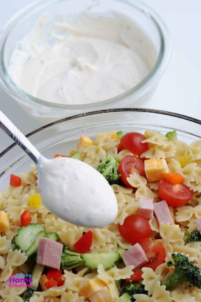 small bowl of dressing in background, spoon with dressing over top of pasta salad.