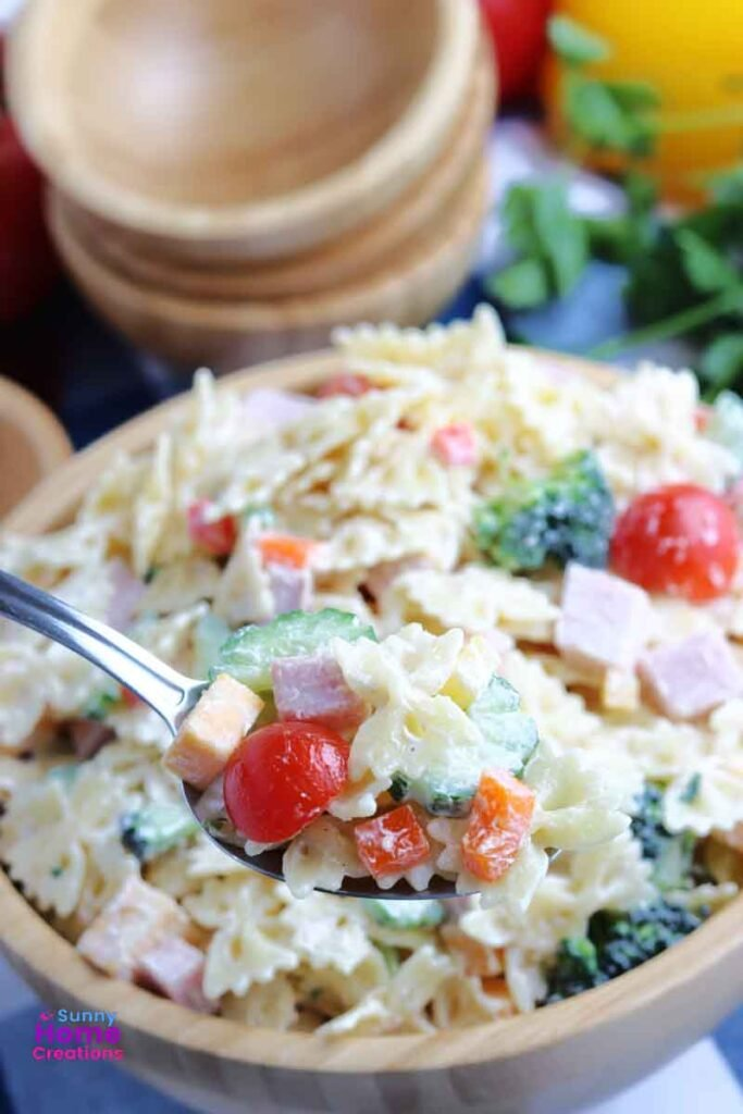Big bowl of pasta salad with a heaping spoonful of pasta salad the main focus.