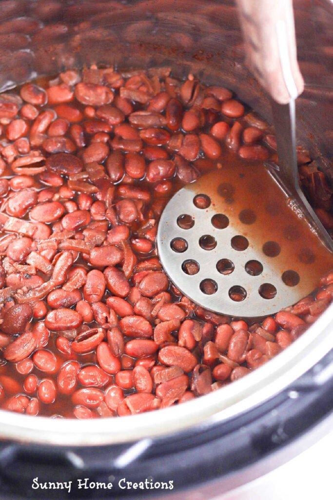 Potato masher, mashing the beans.