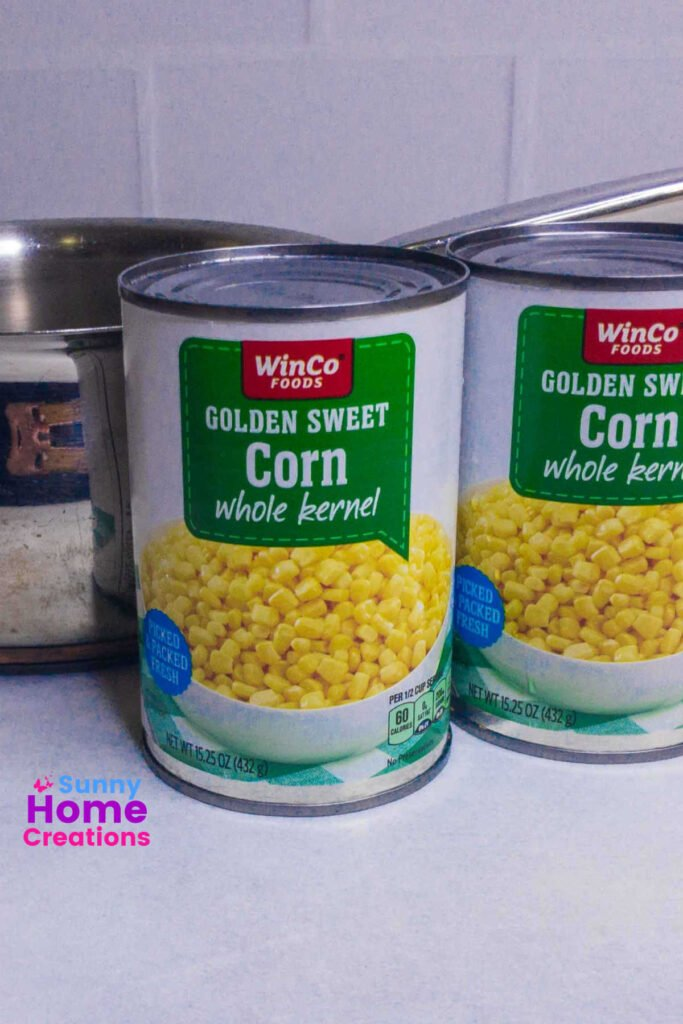 two cans of sweet corn and part of a saucepan.