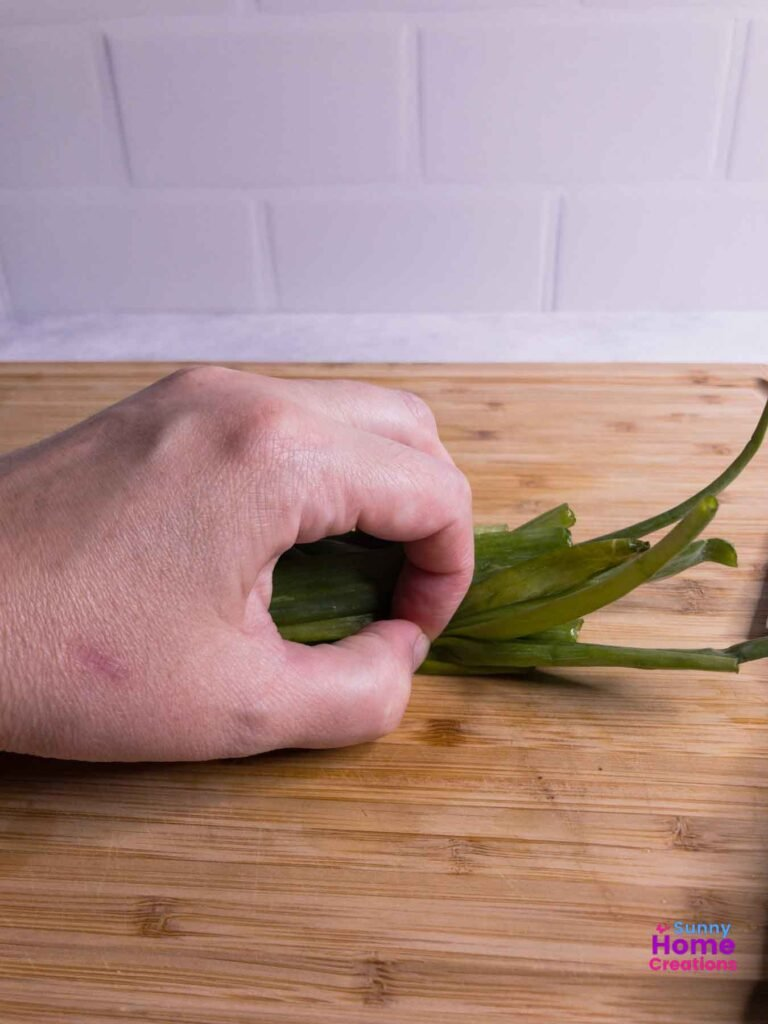 Hand holding green onion stems on a cutting board.