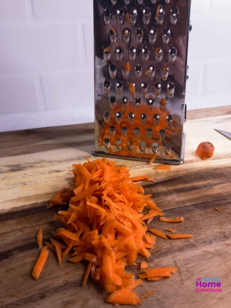 shredded carrots on cutting board with grater in background.